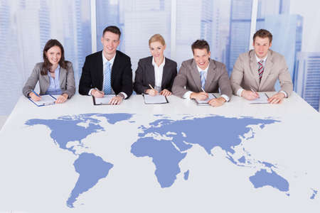 Portrait of confident business people sitting at conference\ table with world map.