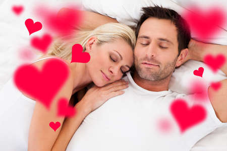Digital composite image of loving young couple sleeping in bed photo
