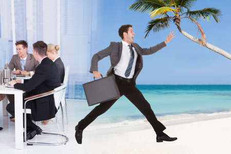 Full length of businessman escaping from conference meeting towards beach for vacation photo