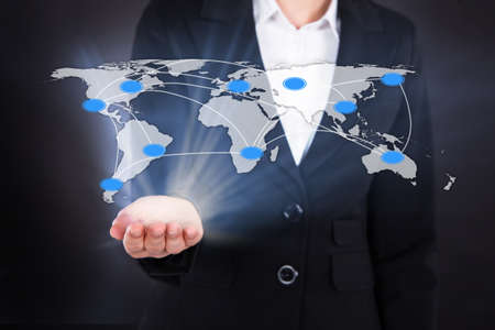 Digital composite image of businesswoman showing connected world map representing globalization. photo