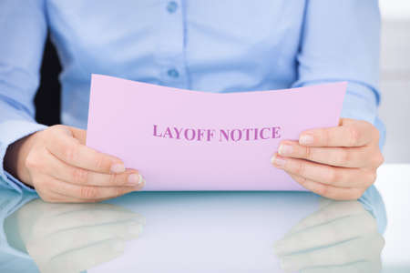 layoff: Midsection of businesswoman reading layoff notice at desk