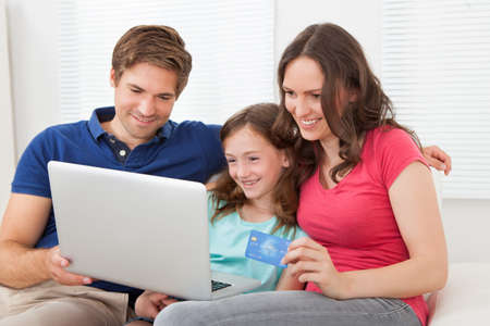 Happy family of three using laptop and credit card to shop online on sofa at home Foto de archivo