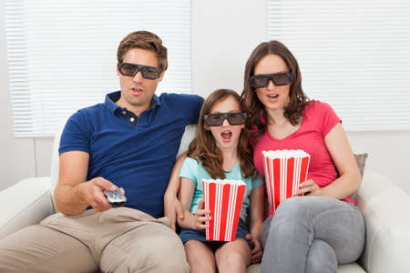 Shocked family in 3D glasses having popcorn while watching movie at home photo