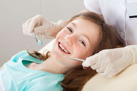 dentist and patient: Portrait of happy girl undergoing dental treatment at clinic