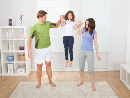 Full length of fit parents picking up daughter while exercising at home photo