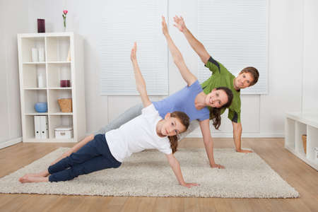 plank position: Full length portrait of fit family doing side plank yoga on rug at home