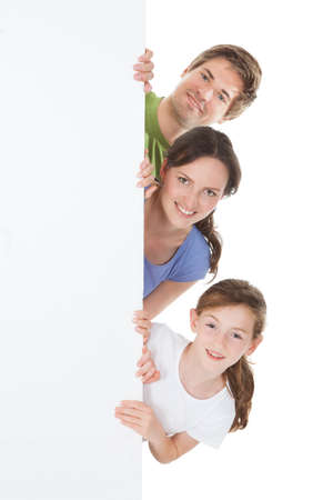Portrait of happy family peeking from blank billboard over white background photo
