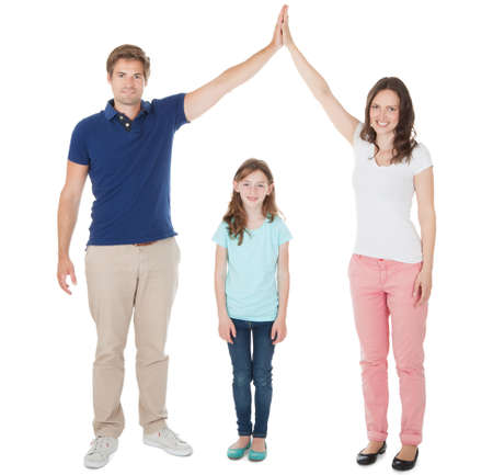Full length portrait of parents forming house roof shape above daughter over white background photo