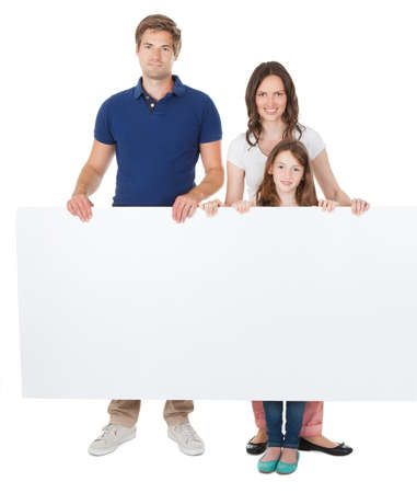 man holding sign: Portrait of confident family holding blank billboard over white background Stock Photo