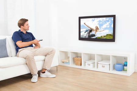 Full length of man watching TV in living room at home photo