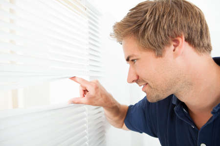 venetian blind: Side view of mid adult man peeking through blinds at home Stock Photo