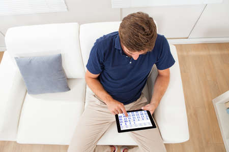 High angle view of man using calendar on digital tablet in living room at home photo