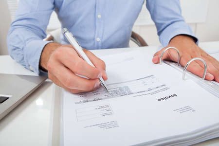 cropped: Cropped image of businessman calculating invoice at desk in office