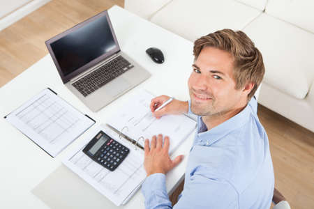 calculations: High angle portrait of businessman calculating tax at desk in office