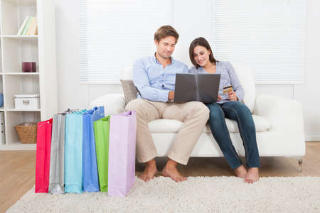 Happy young couple shopping online with bags on sofa at home