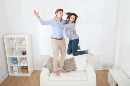 Full length of playful couple jumping on sofa at home Reklamní fotografie