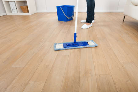 cleaning floor: Low section of young woman mopping hardwood floor at home Stock Photo