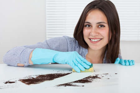 Close-up of womans hand cleaning dirt on table with sponge at home Stock Photo