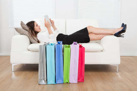 surf shop: Full length side view of young businesswoman using digital tablet with shopping bags on floor at home