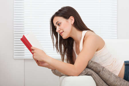 Full length side view of young woman reading book while lying on sofa at home photo