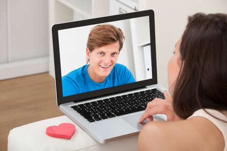 Geerntetes Bild der jungen Frau, Video-Chats mit ihrem Freund auf Laptop zu Hause Standard-Bild