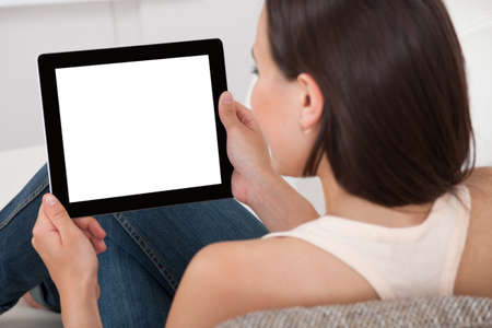 Portrait of beautiful young woman holding digital tablet with blank screen on sofa at home