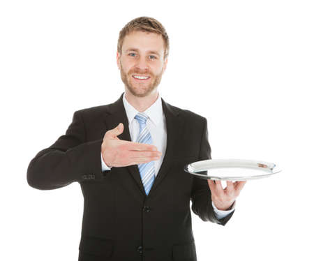 Portrait of mid adult businessman holding empty tray over white background photo