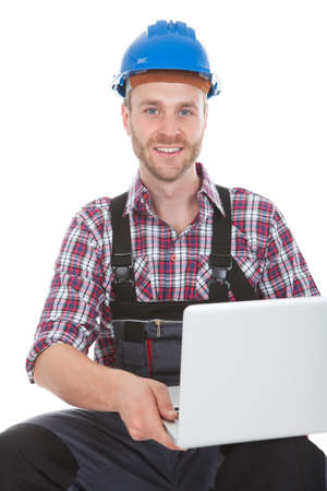 Full length portrait of confident manual worker using laptop while sitting on trunk over white background photo