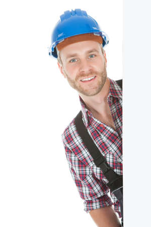 Full length portrait of confident young manual worker holding billboard over white background photo