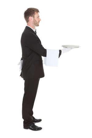 Full length side view of waiter holding empty tray isolated over white background photo