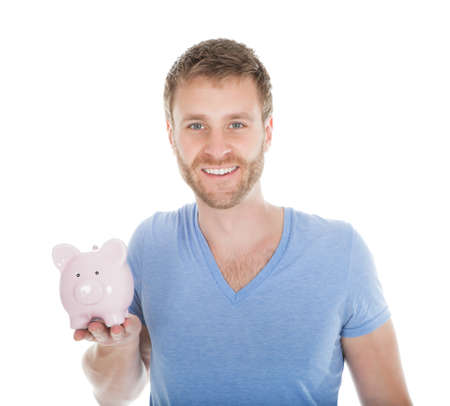 coinbank: Portrait of mid adult man holding piggybank over white background