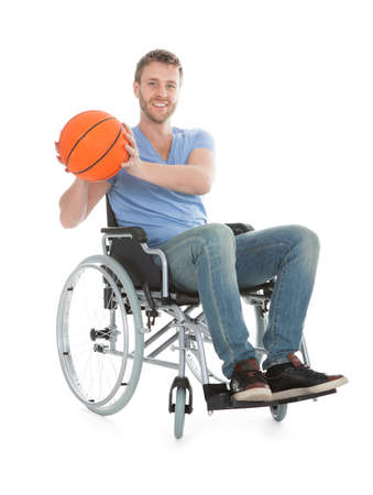 Full length portrait of disabled player holding basketball on wheelchair over white background photo