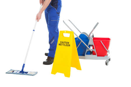 Low section of male servant mopping floor by Wet Floor Sign over white background Stockfoto