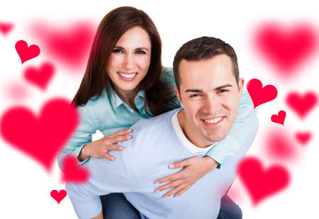 young couple smiling: Portrait of loving young man piggybacking girlfriend over white background