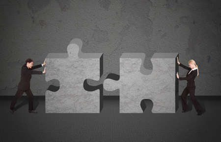 Full length side view of business people joining puzzle pieces photo
