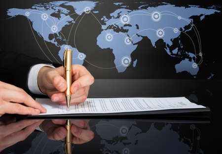 international business agreement: Cropped image of businessman signing contract with world map in background.