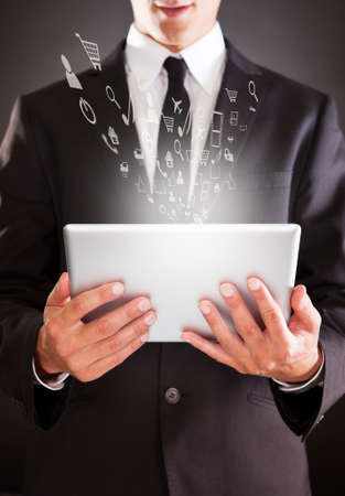 Midsection of businessman holding digital tablet with virtual icons over colored background photo