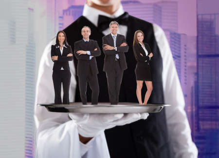 Confident business people standing on silver tray being carried by waiter photo