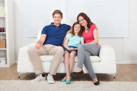 Full length portrait of smiling family sitting on sofa at home Stock Photo