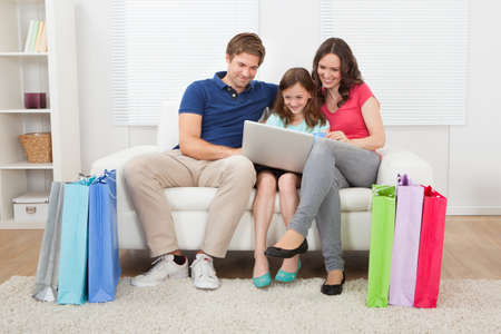 Happy family with shopping bags using laptop while relaxing on sofa at home