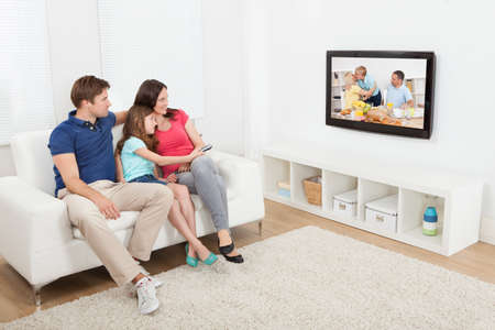 Longitud total de la familia cariñoso viendo la televisión juntos en casa Foto de archivo