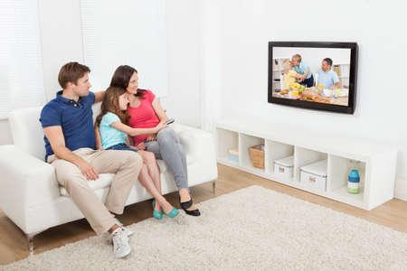 Volledige lengte van aanhankelijk familie tv kijken samen thuis