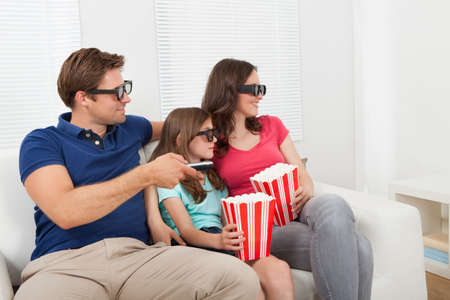 big screen tv: Smiling family in 3D glasses having popcorn while watching movie at home Stock Photo
