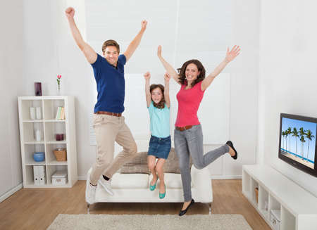 Full length portrait of excited family with arms raised jumping in living room at home Stock Photo