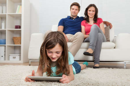 Girl using digital tablet on rug while parents sitting in background at home photo