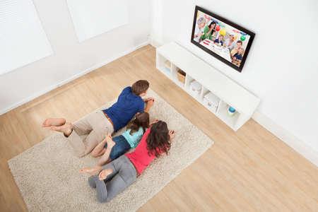 Familia de tres viendo la televisión mientras está acostado sobre la alfombra en casa