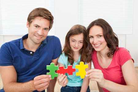 Portrait of happy family joining puzzle pieces at home photo