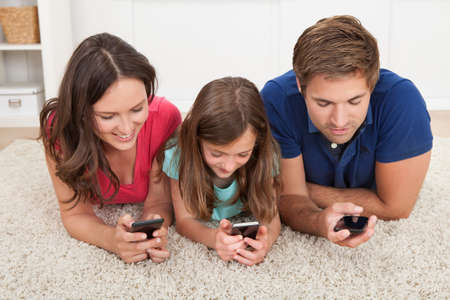 adult child: Family using smart phones while lying on rug at home