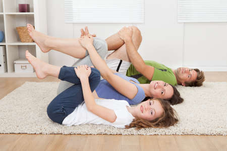 Full length portrait of healthy family practicing yoga on rug at home photo