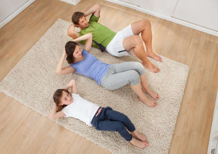 rug: High angle view of family doing situps on rug at home Stock Photo